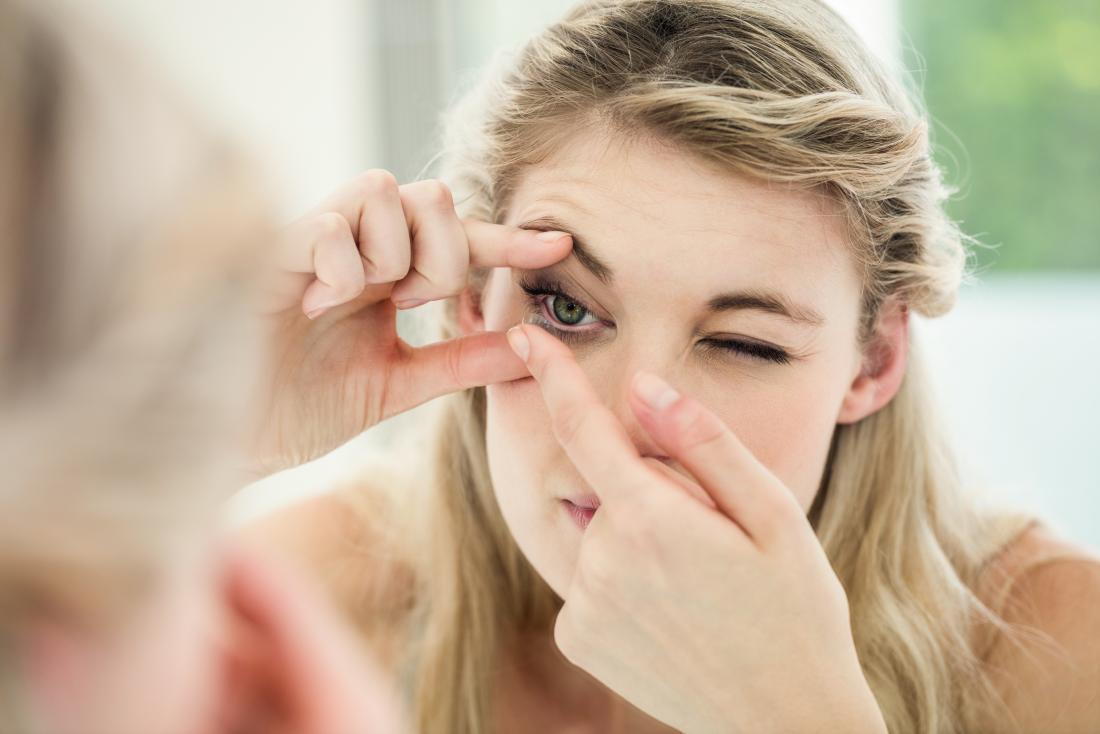 jovem mulher colocando em contato lente