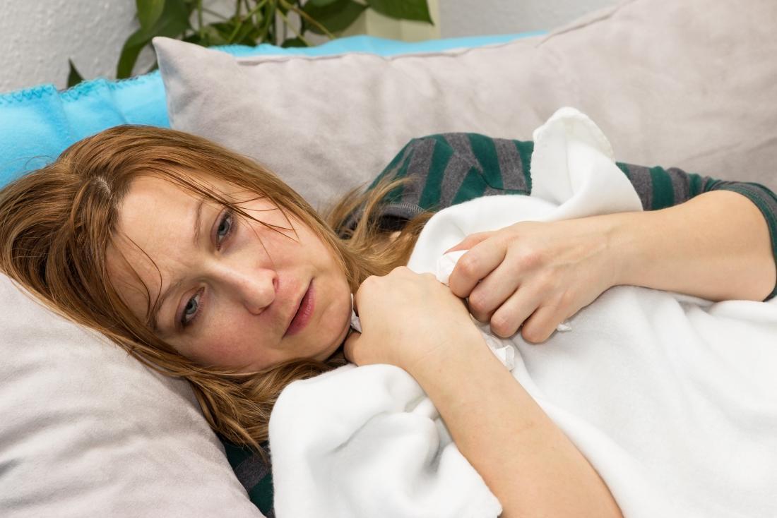 Kobieta na kanapie z kocem, cierpi na gorączkę, pocenie się i dreszcze.