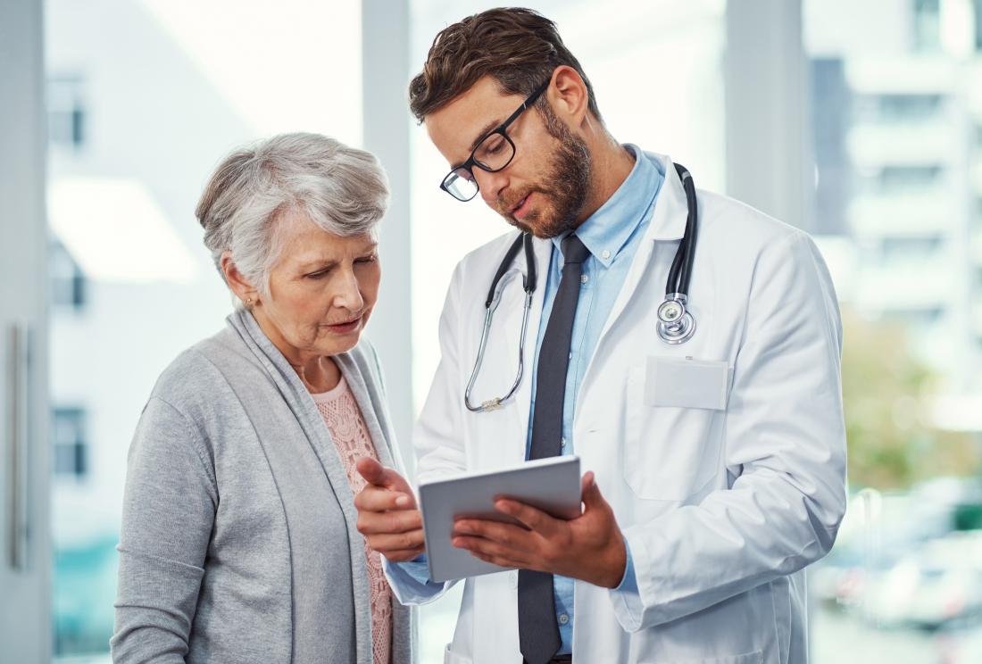 Млад мъжки лекар, който говори с зряла пациентка.