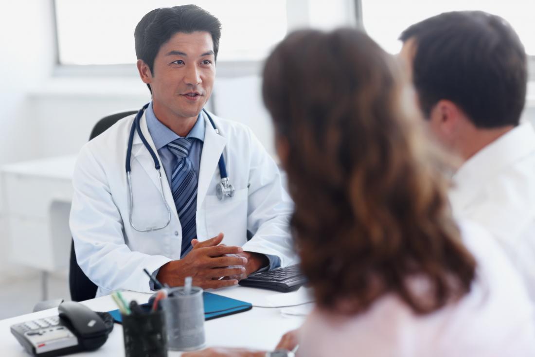 Docteur parlant à un couple pour aider à la planification familiale.
