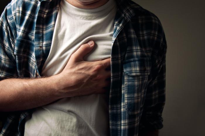 Mann hält sein Herz