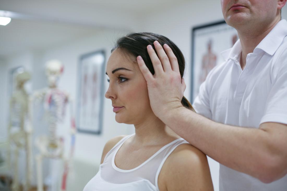 Frau, die ihren Kopf und Hals manipuliert vom Chiropraktor hat.