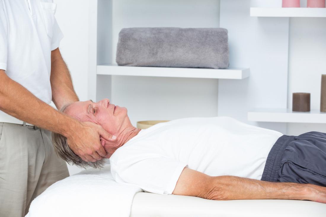Älterer Mann, der Kopf- und Stutzenmassage vom Chiropraktor empfängt.