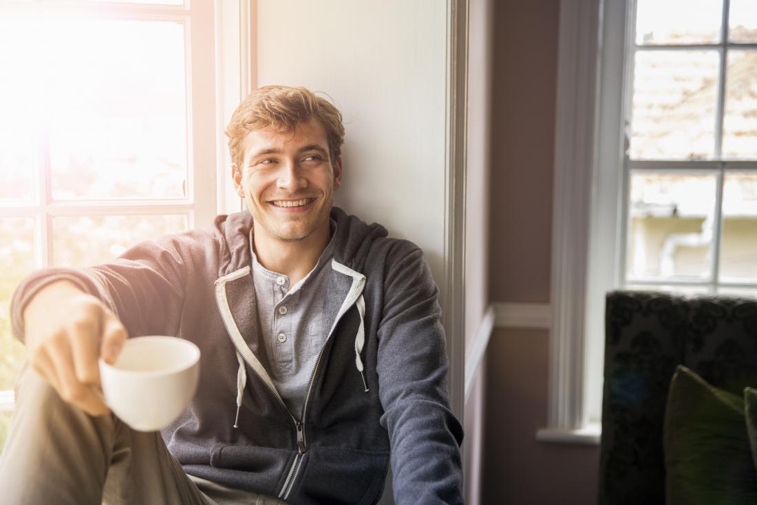 усмихнат млад мъж, държащ кафе чаша