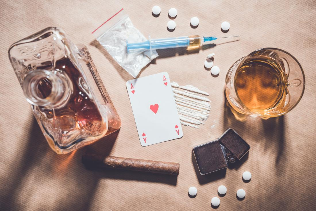 Diverses substances addictives sur une table, y compris l'alcool, les drogues, l'allume-cigare et une carte de jeu.