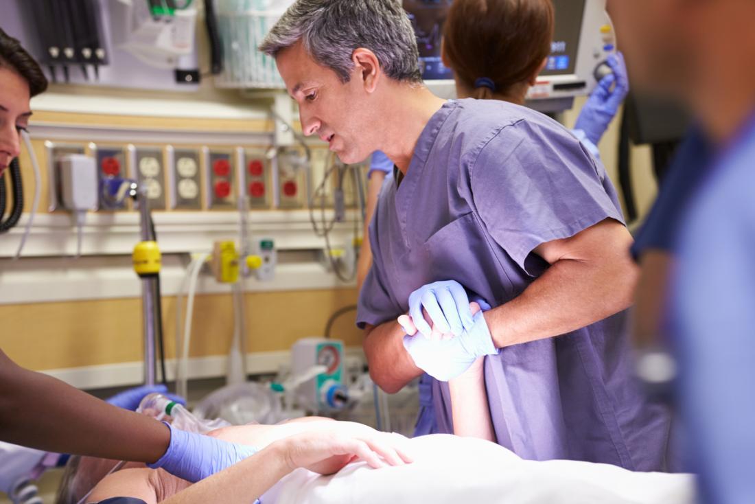 Docteur tenant la main du patient sur le lit d'hôpital dans la salle d'urgence.
