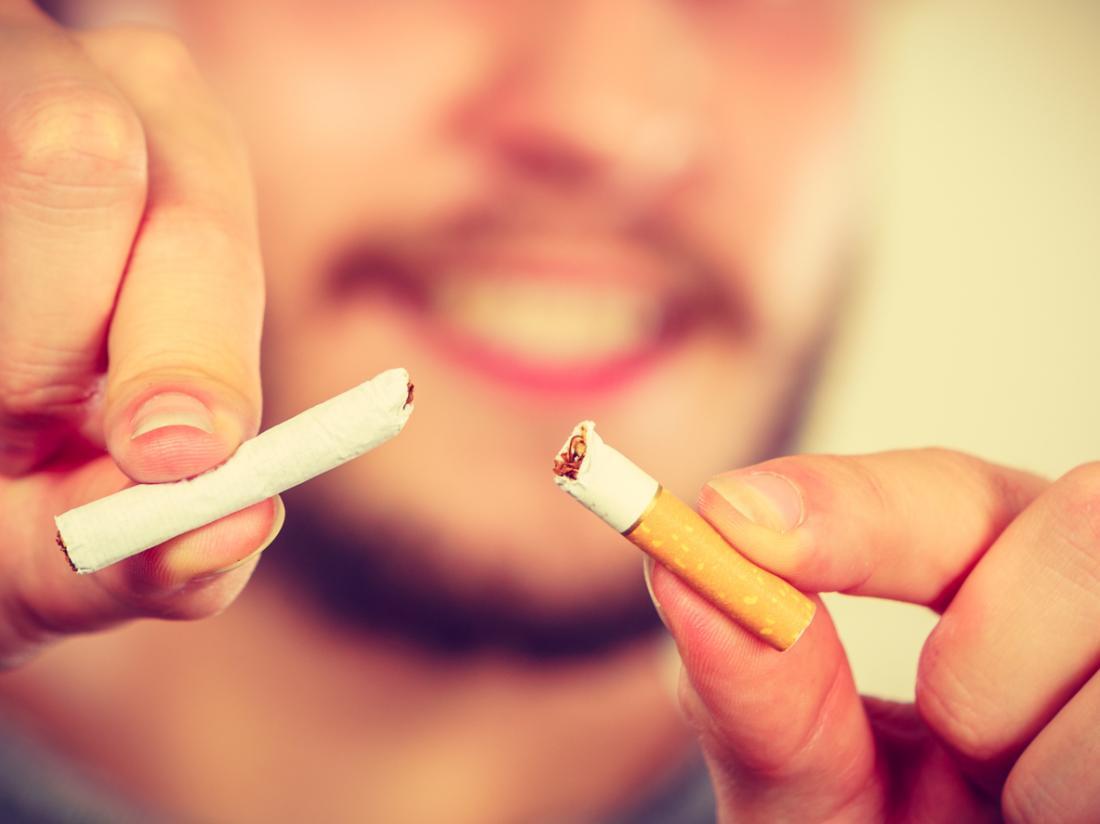 Mann bricht Zigarette in zwei Hälften