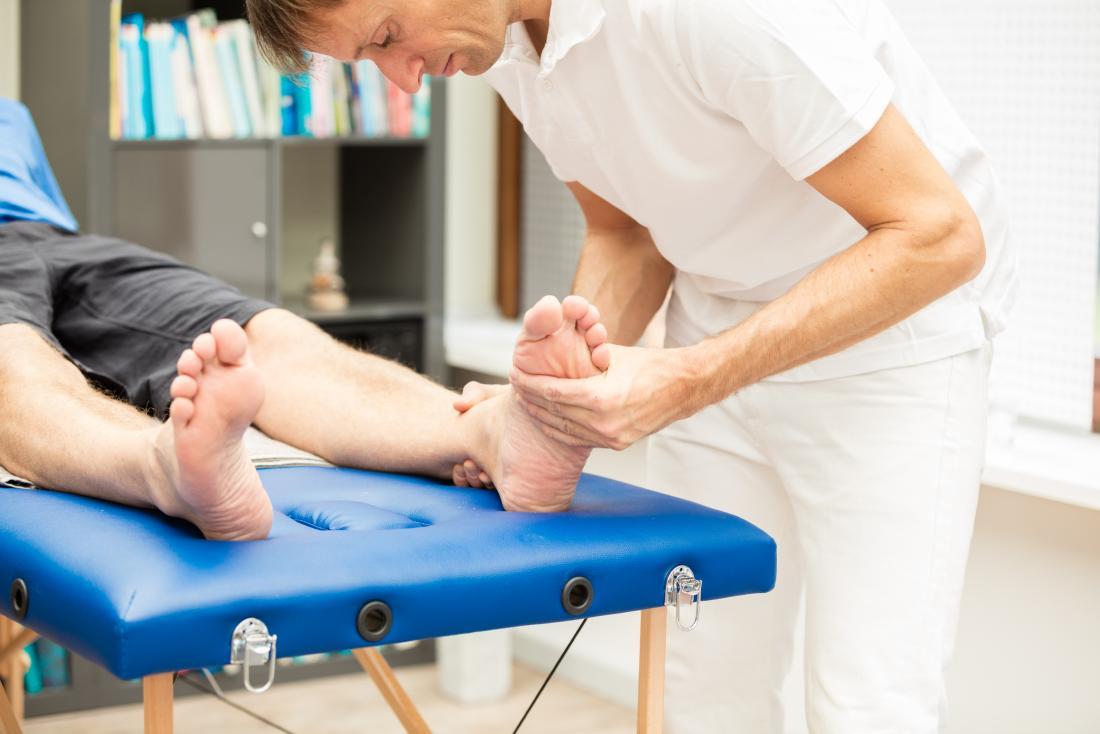 Podologe, der die Füße des Patienten kontrolliert.