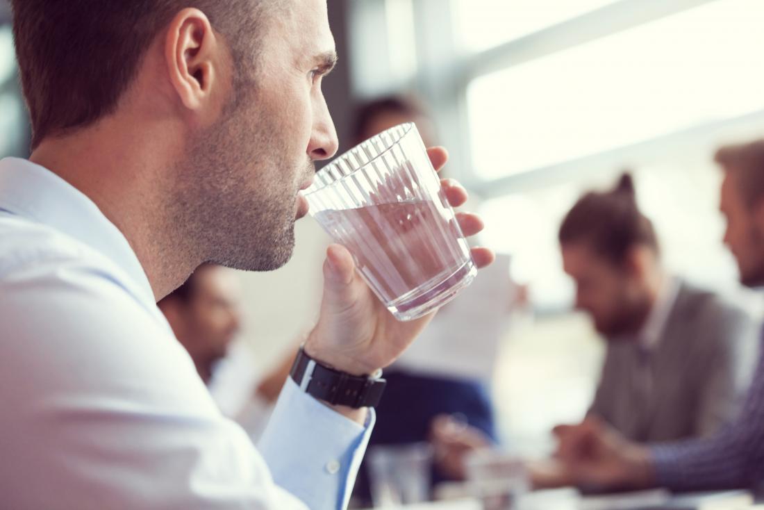 Човек пие вода от стъкло.