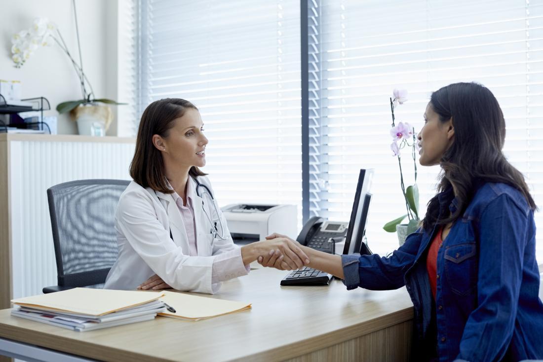 Doktorski lub terapeuta trząść ręki z pacjentem w biurze.