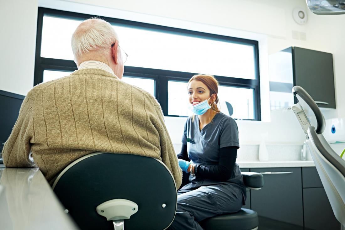 Älterer Patient, der mit jungem Zahnarzt spricht.