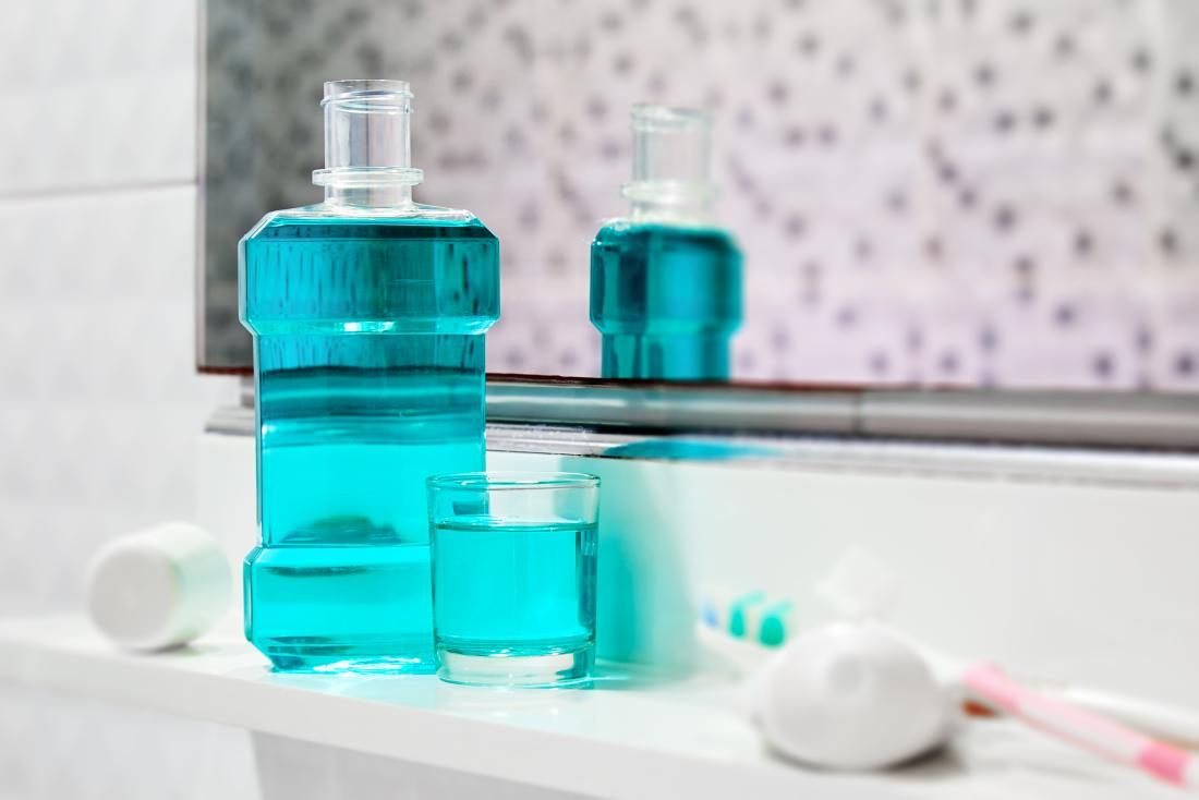 Antiseptisches Mundwasser und Zahnpasta auf Badezimmerregal vor Spiegel.