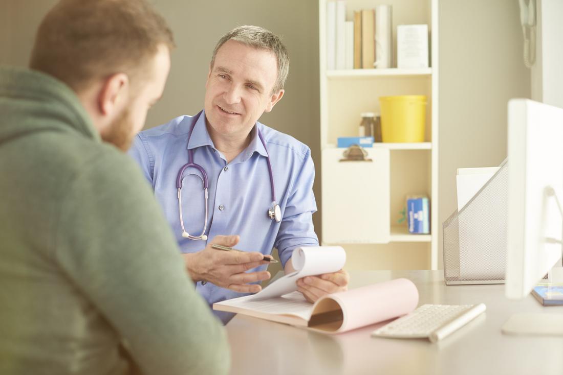 Jeune patient masculin parlant à un médecin de sexe masculin.