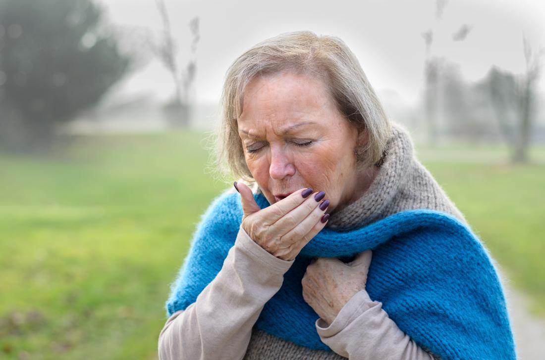 По-възрастна дама, която кихне в ръката си и може да разпространи пневмококов менингит