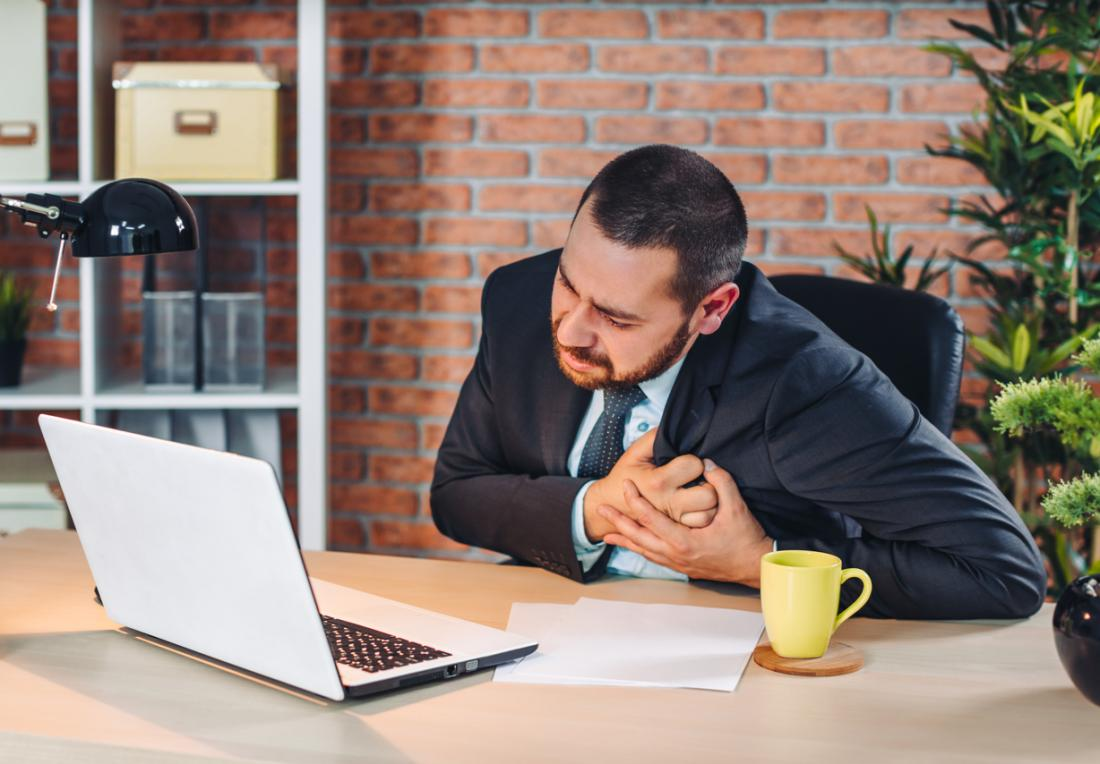 Người đàn ông trong bộ đồ kinh doanh tại bàn ôm ngực đau đớn.