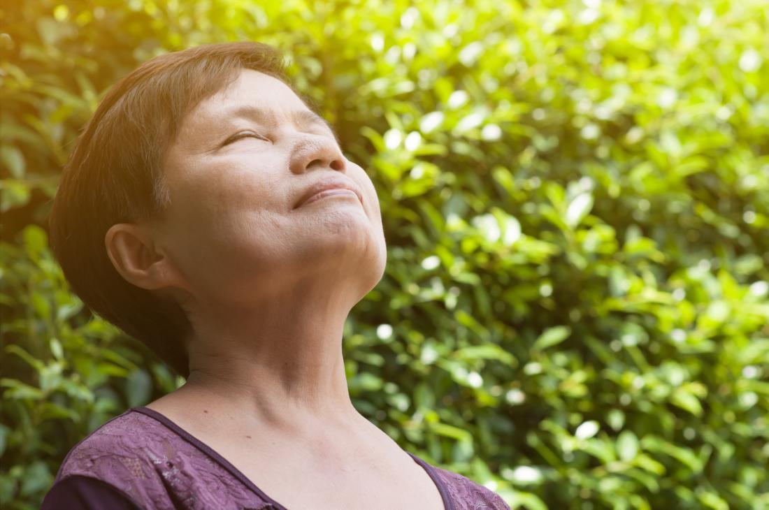Người phụ nữ hít thở sâu bên ngoài, hít thở không khí trong lành.