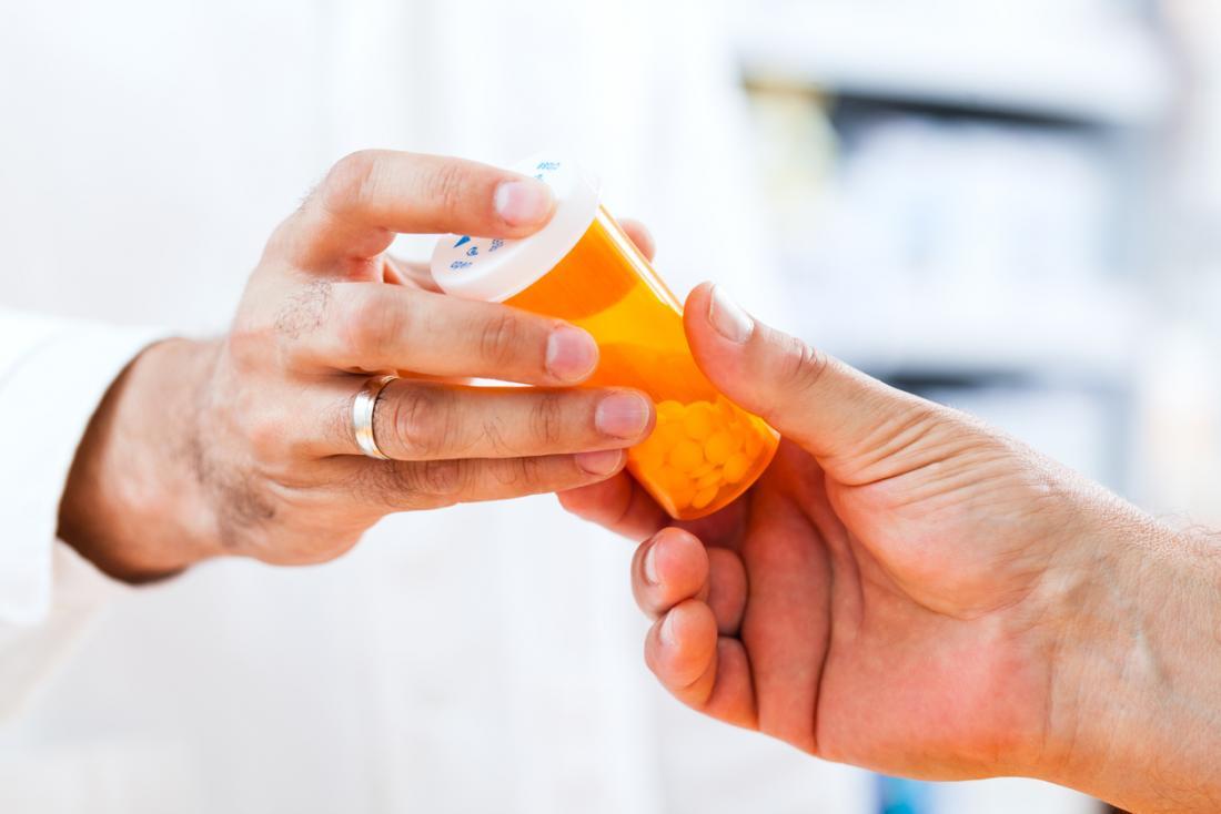 Фармацевт, даващ на пациента бутилка хапчета.