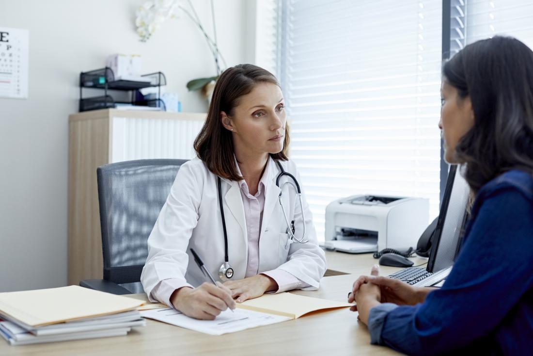 Женски лекар и пациент обсъждат лечението и приемат медицинска анамнеза.