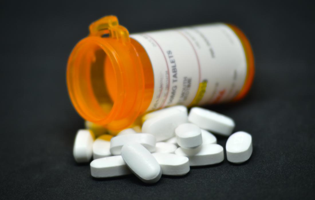 Bouteille de médicaments antidouleur, avec pile de pilules au premier plan.