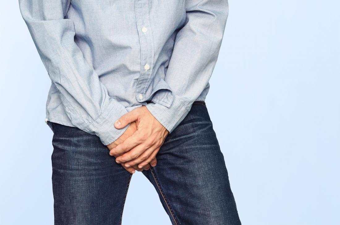 Mann in Jeans mit Skrotal-Ekzem bedeckt seinen Schritt mit seinen Händen.