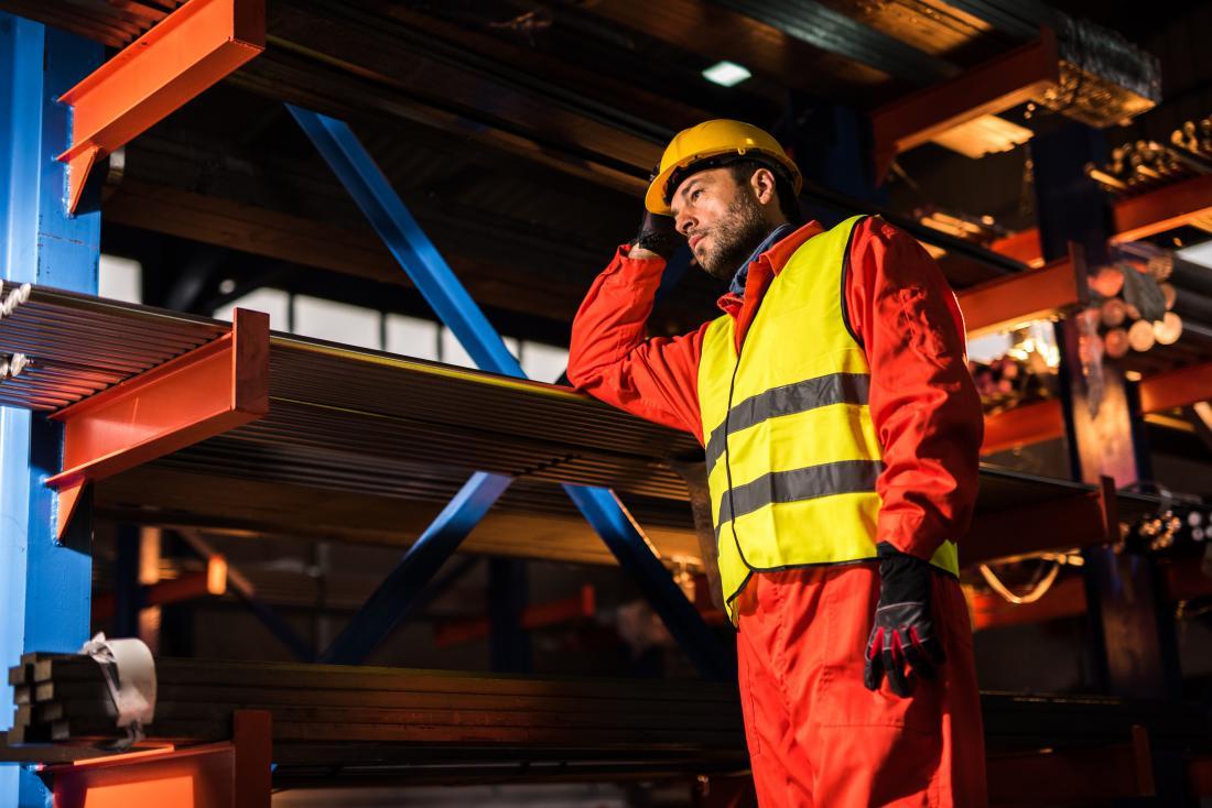 Mann, der in der industriellen Fabrikumgebung mit Schutzausrüstung und Sturzhelm arbeitet.