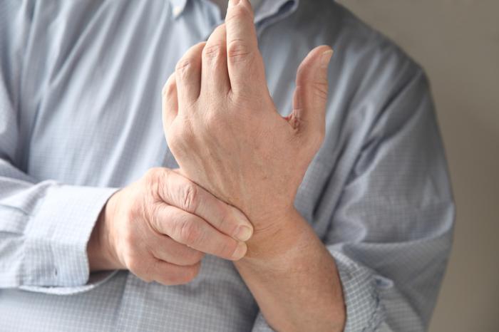 Un uomo tiene il polso con la mano sinistra