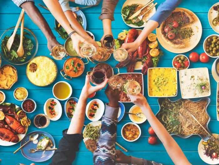 uma mesa cheia de comida mediterrânea e pessoas bebendo vinho