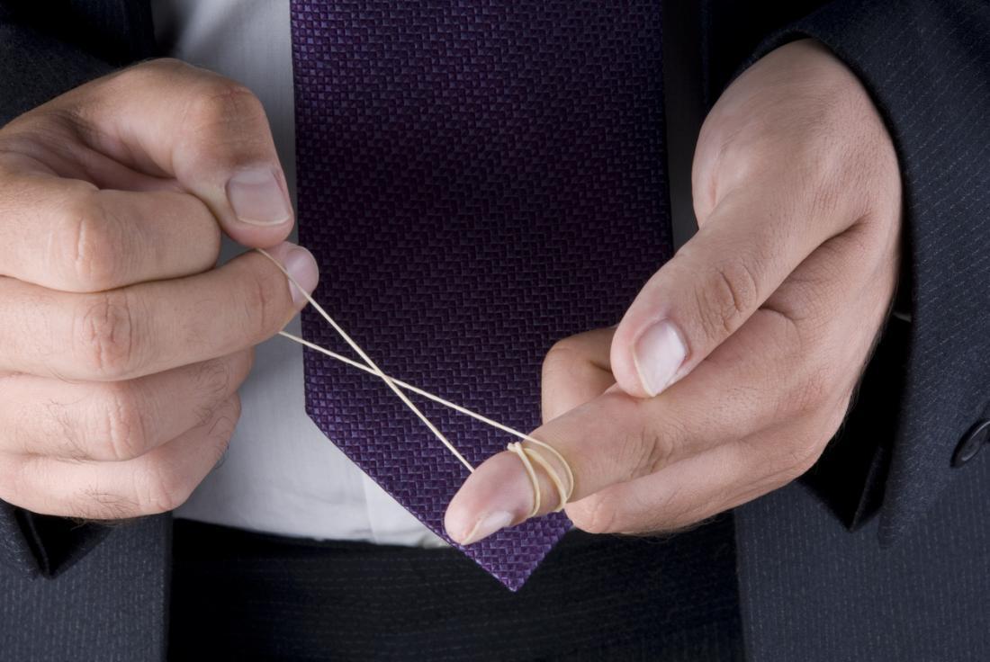 Човек в бизнес костюм обвива еластична лента около пръст.