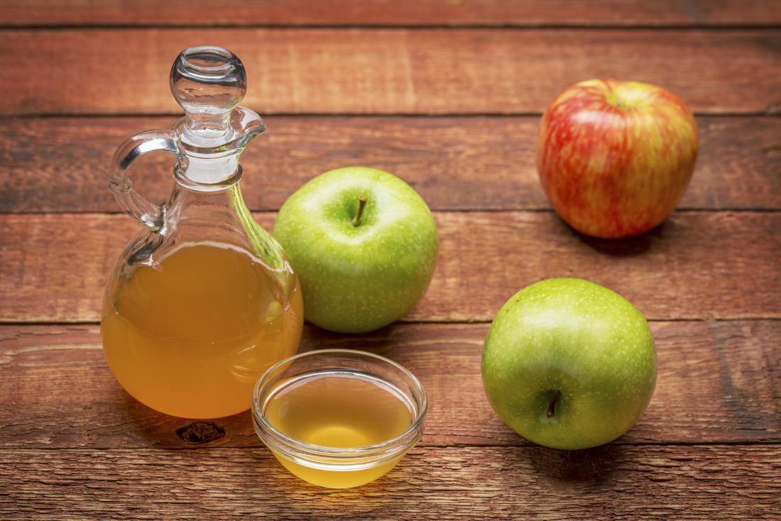 Vinagre de maçã para a desintoxicação no frasco e na bacia de vidro ao lado da tabela de madeira das maçãs verdes e vermelhas n.