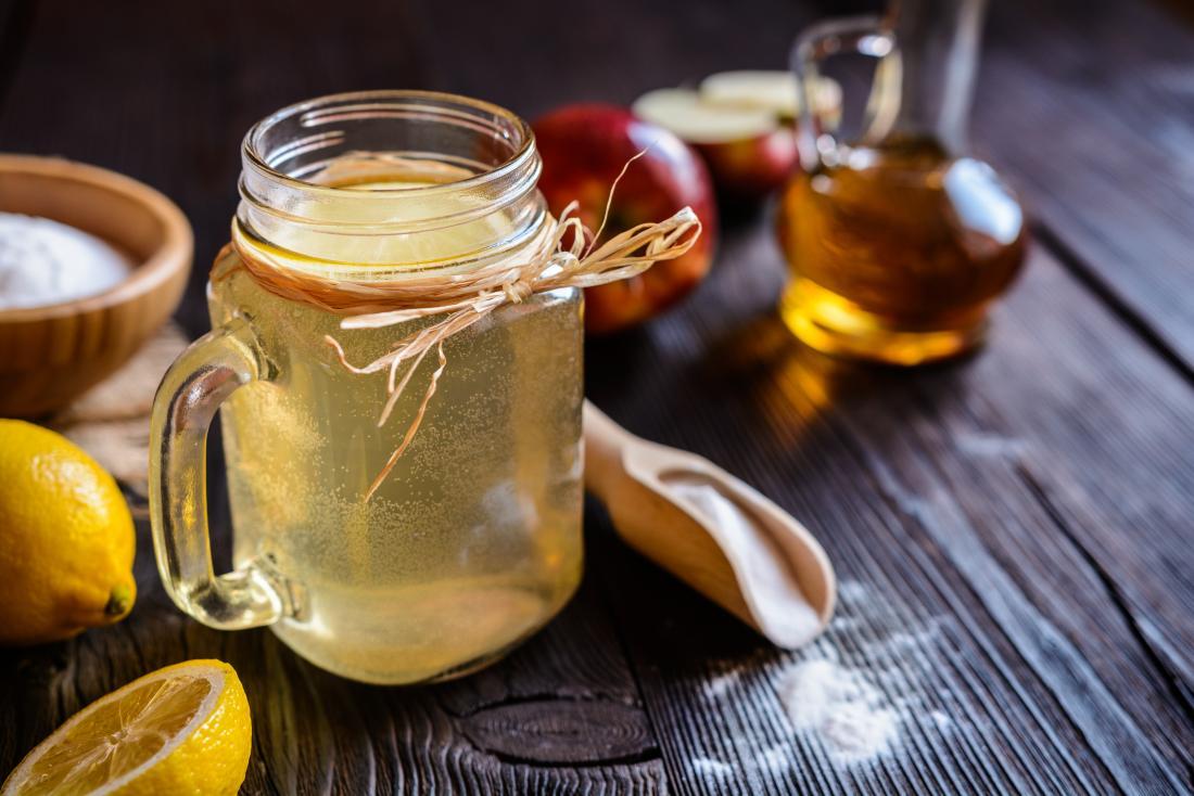 O vinagre de cidra de Apple usado para fazer a desintoxicação bebe com suco e açúcar de limão no frasco de pedreiro de vidro.