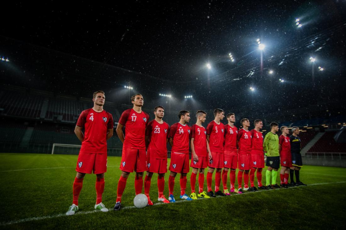Một đội bóng đá xếp hàng trên sân cỏ
