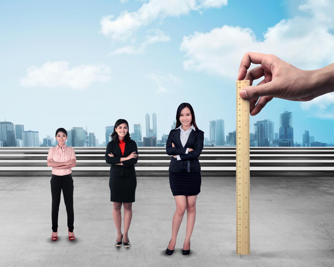Mulheres de diferentes alturas ao lado de uma régua tentando calcular a estatura média das mulheres