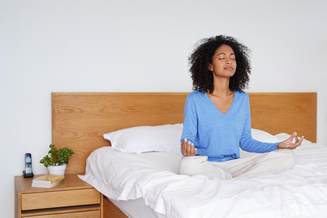yatakta meditasyon oturan genç kadın
