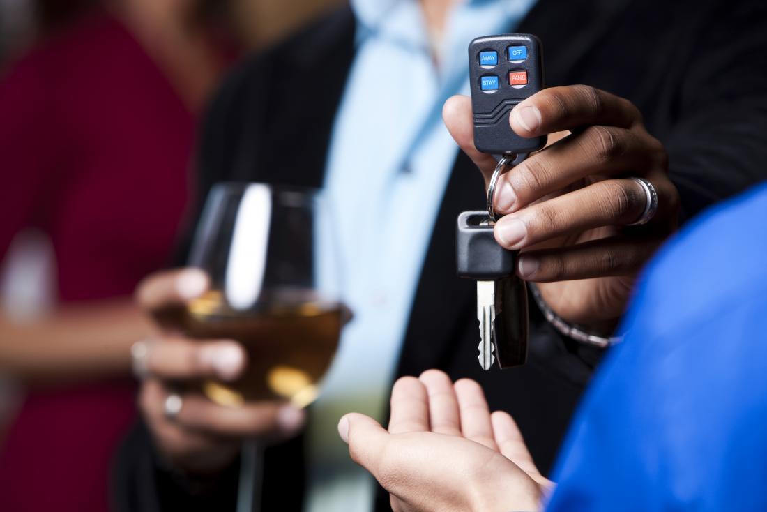 adam elinde alkollü bir içecek ile anahtarlarını teslim