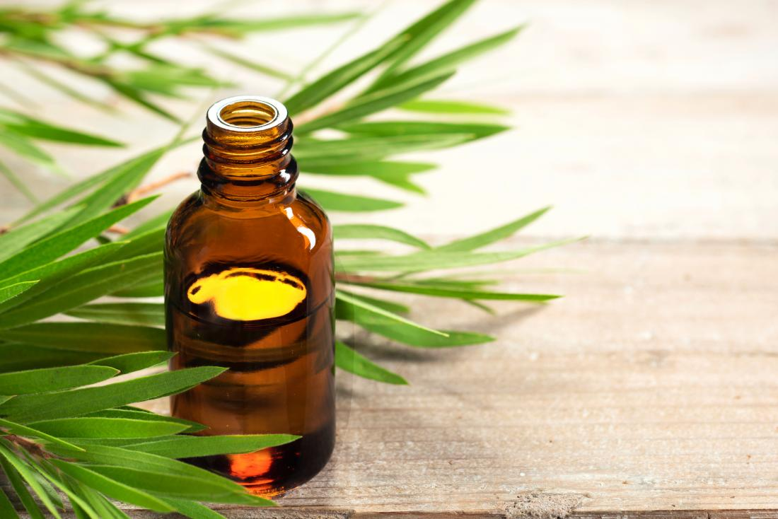 Етерично масло от чаено дърво за лечение на краста в стъклен буркан с листа на фона.