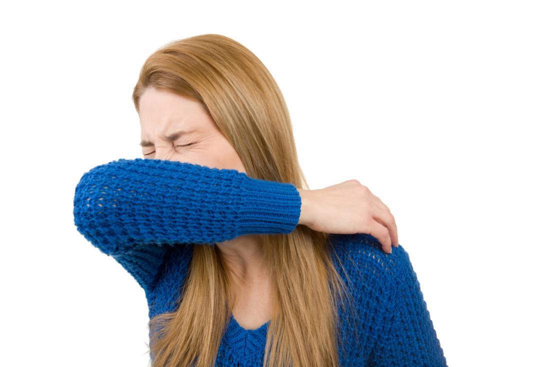 彼女の肘にくしゃみをする女性