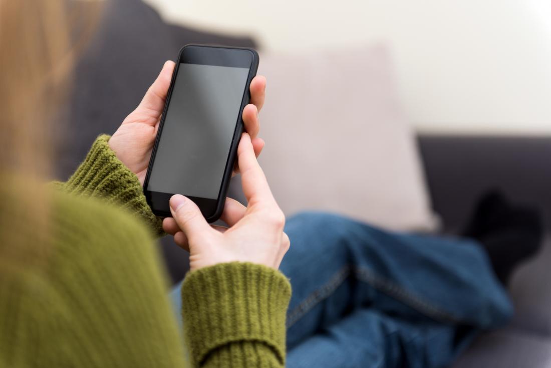 Bir akıllı telefona bakarak koltukta oturan