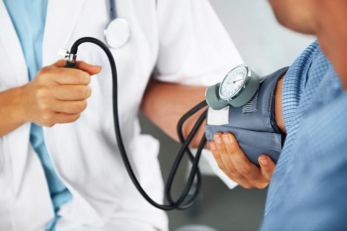 Um médico leva a pressão arterial de um homem
