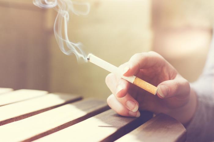 Uma pessoa segura um cigarro aceso na mão direita