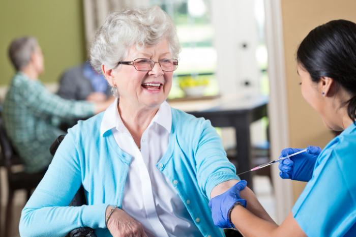 Eine Grippeimpfung, die von einem Doktor auf einem Patienten verabreicht wird
