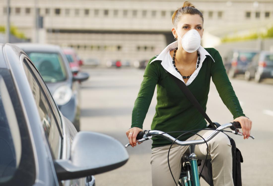 Mulher que dá um ciclo através da máscara vestindo da poeira e da poluição da cidade.