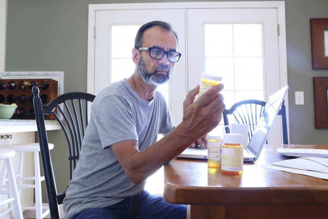homme de baby-boomer mature vérifiant les bouteilles de médicaments.