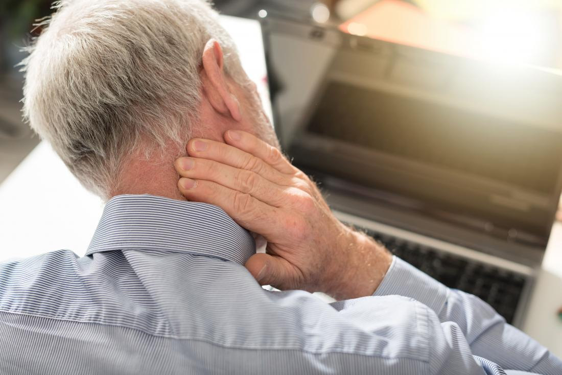 Homem com dor de cabeça na parte de trás da cabeça esfregando o pescoço.