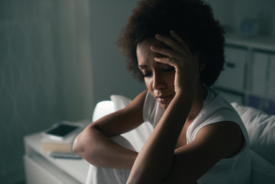 Mulher sentada na cama com dor de cabeça e insônia.
