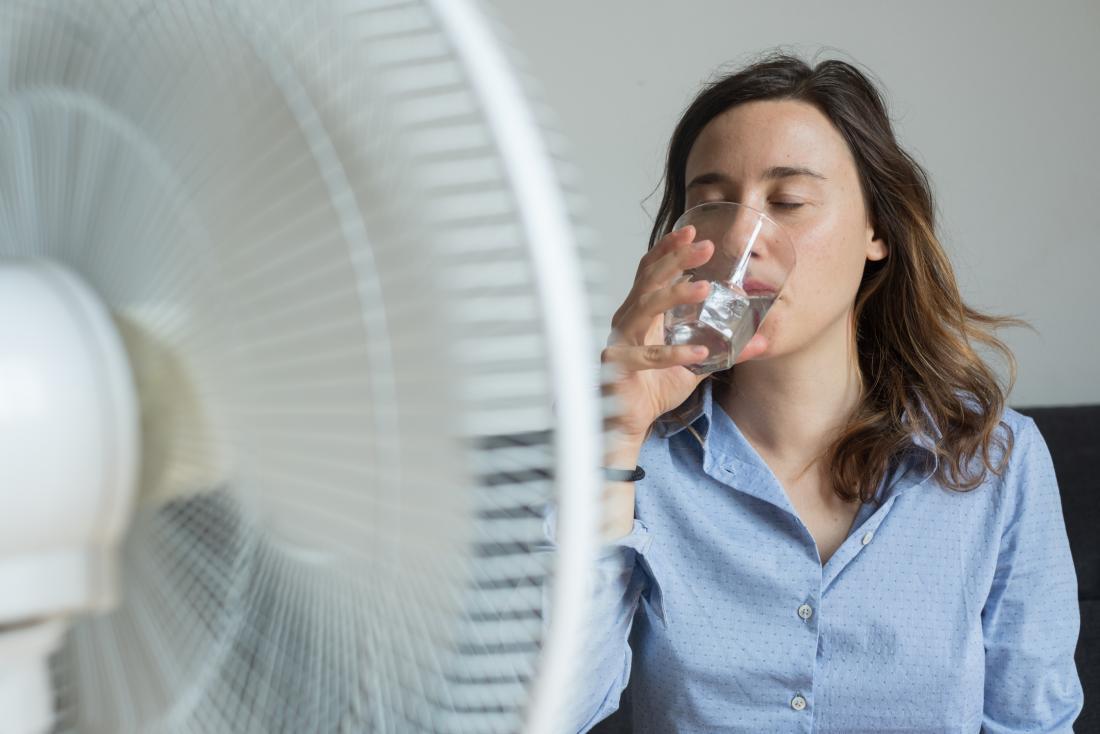 млада жена, пиейки вода пред вентилатор