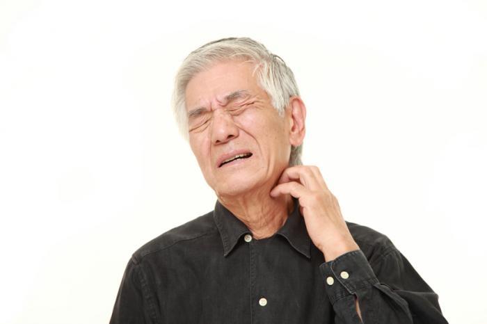 不快感に見える高齢の男性は、左手で首を傷つける。