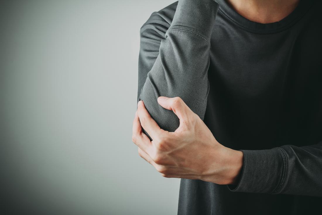 homem segurando o cotovelo em dor devido a um cotovelo hiperextendido