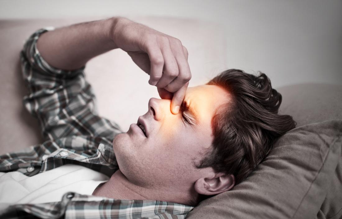 Mann hält seine Nase wegen eines Sinus Kopfschmerzen