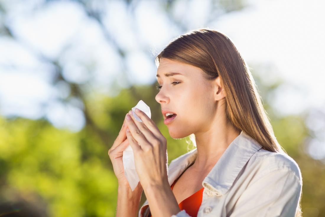 Frau Niesen mit Heuschnupfen, die ähnliche Symptome wie Sinus Kopfschmerzen haben können
