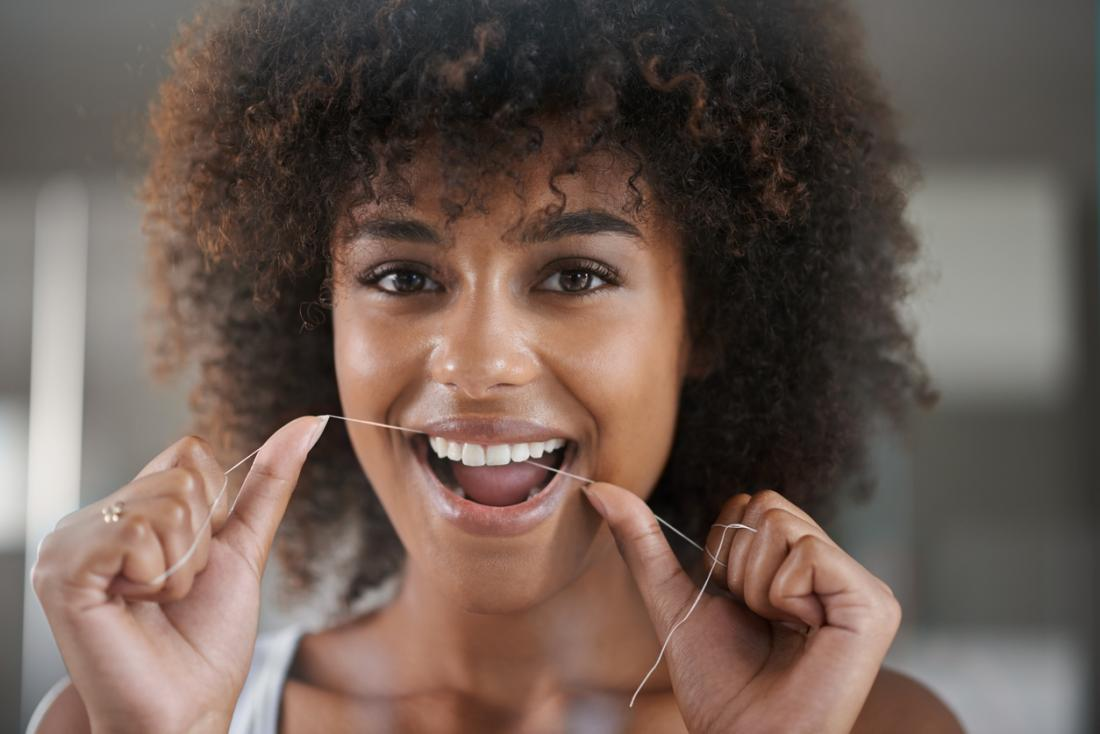 女性は彼女の歯をflossing